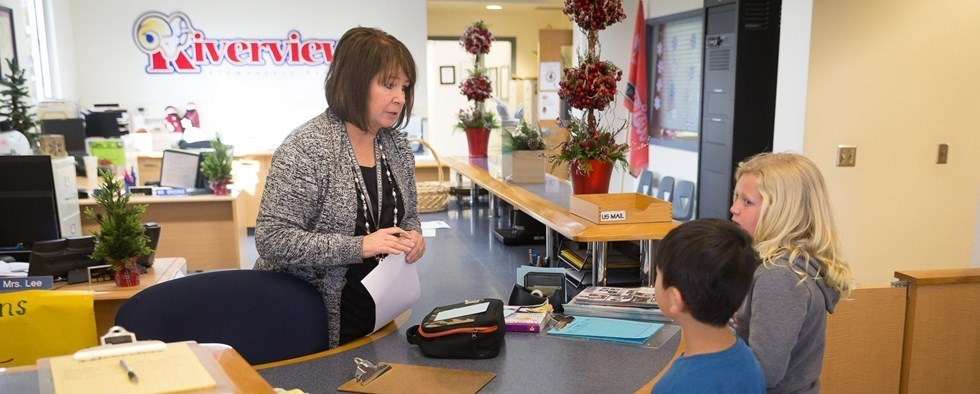 Employee at desk helping children